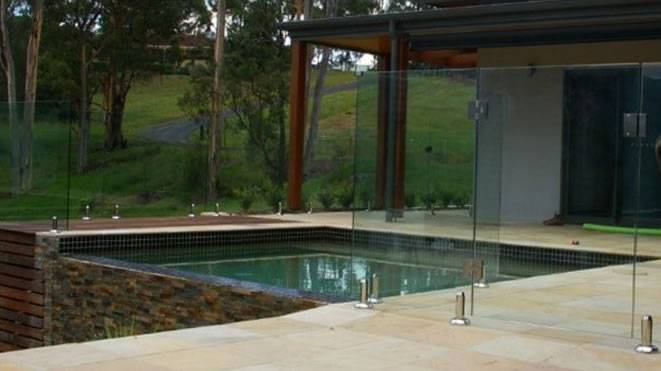 At work installing a frameless glass pool fence in Adelaide suburbs