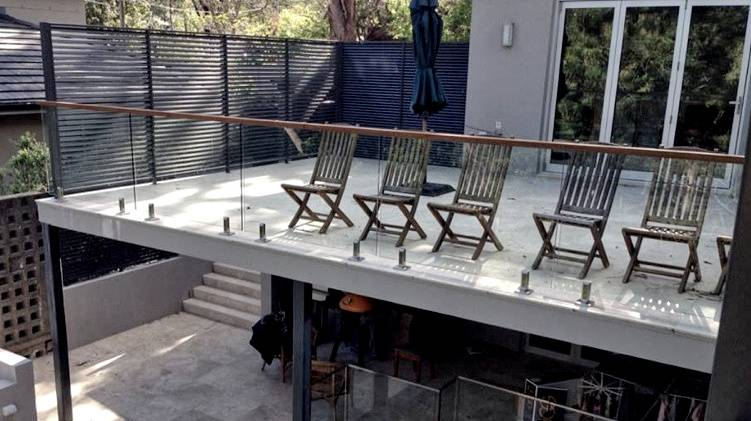 Balcony glass balustrade with custom timber rail. Further balustrade/fencing is utilised below.