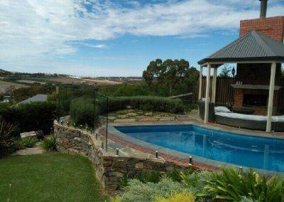 Frameless glass pool fencing installed on a bed of stone retaining wall in an Adelaide suburb